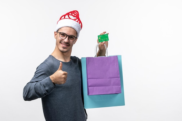 Вид спереди молодого человека с банковской картой и пакетами на белой стене