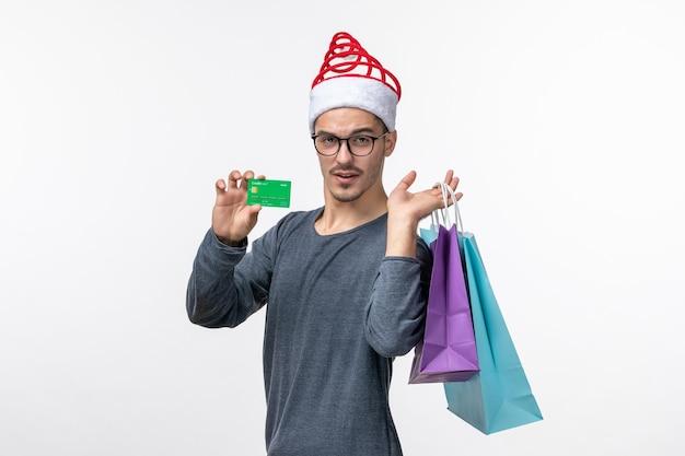 白い壁に銀行カードとパッケージを持つ若い男の正面図