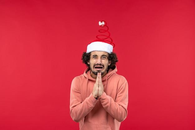 Вид спереди молодого человека с выражением мольбы на красной стене