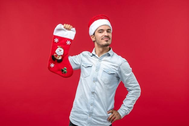 빨간 벽에 크리스마스 양말과 젊은 남자의 전면보기