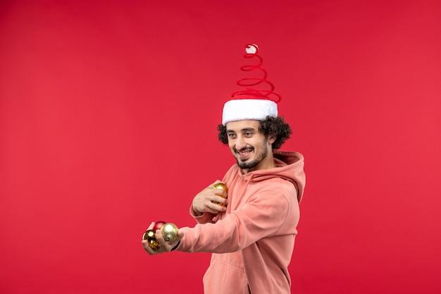 Вид спереди молодого человека с елочными игрушками на красной стене
