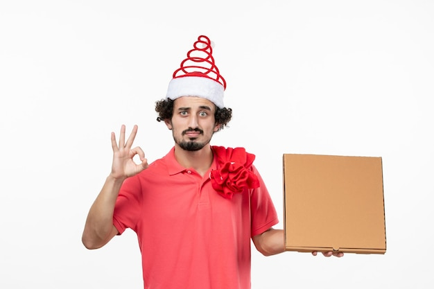 白い壁に配達フードボックスを持つ若い男の正面図