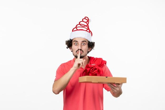흰 벽에 배달 음식 상자가 있는 젊은 남자의 전면 보기