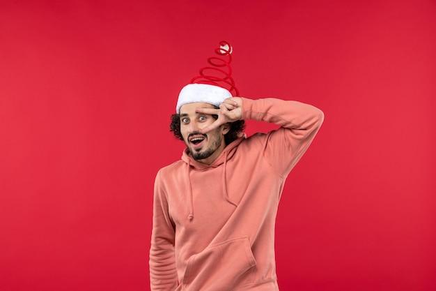 붉은 벽에 흥분된 표정으로 젊은 남자의 전면보기 무료 사진
