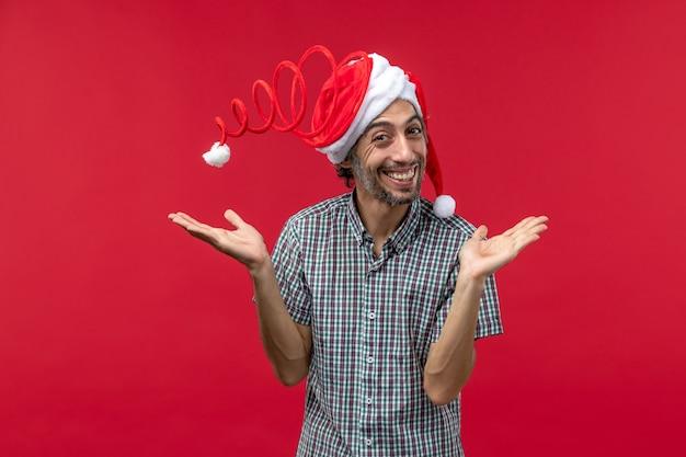 赤い壁に面白いおもちゃの帽子と若い男の正面図