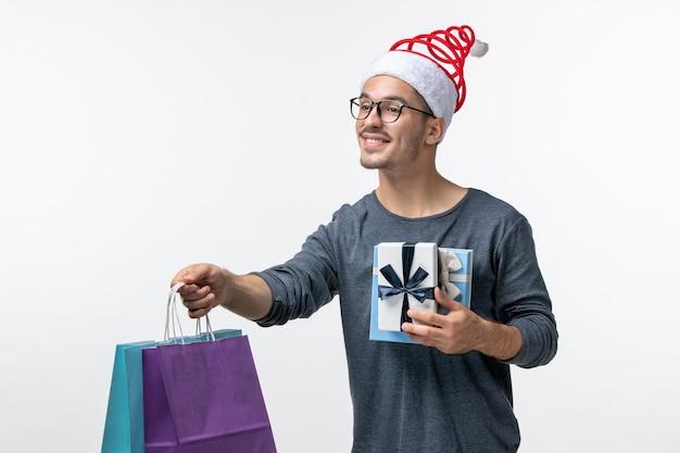 Вид спереди молодого человека с праздничными подарками на белой стене
