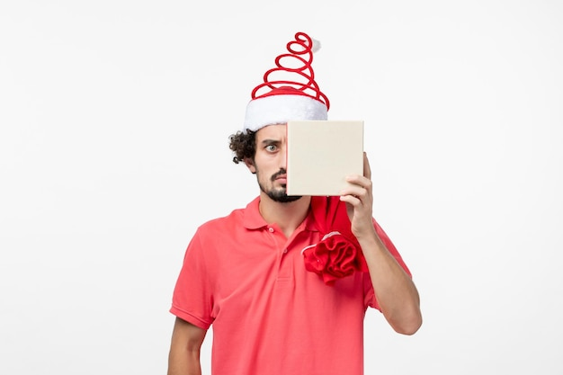 흰색 벽에 휴가 선물을 가진 젊은 남자의 전면 보기