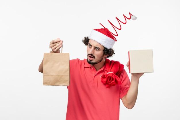 白い壁に休日のプレゼントと若い男の正面図
