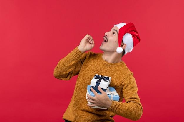 Вид спереди молодого человека с новогодними подарками на красной стене