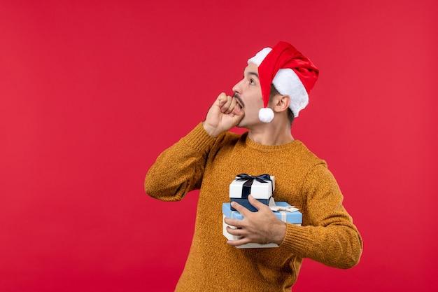 赤い壁に新年のプレゼントと若い男の正面図