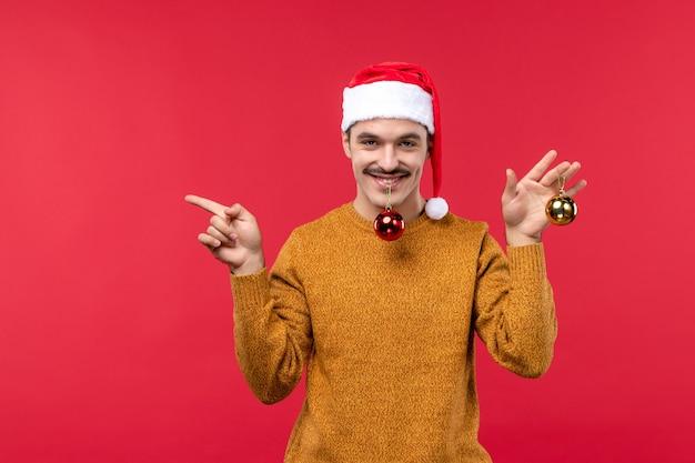 赤い壁にプラスチックのおもちゃを持つ若い男の正面図