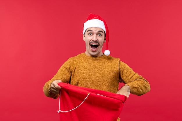 赤い壁にプレゼントバッグを持って若い男の正面図