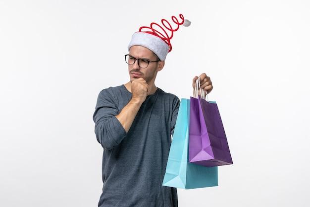 Вид спереди молодого человека с подарками после покупок на белой стене