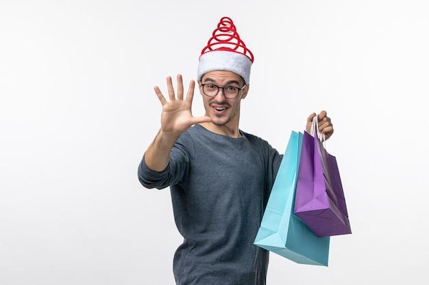 白い壁で買い物をした後のプレゼントと若い男の正面図