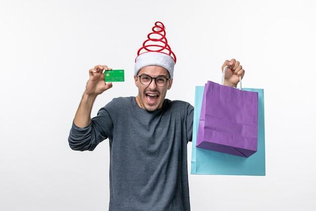흰 벽에 선물과 은행 카드를 가진 젊은 남자의 전면 보기