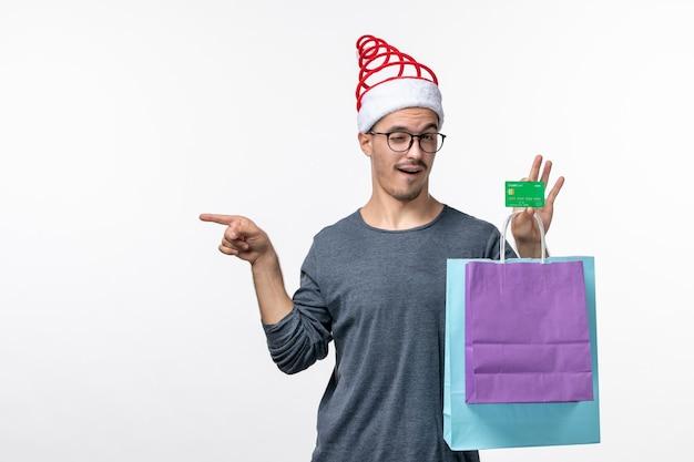 Вид спереди молодого человека с подарками и банковской картой на белой стене