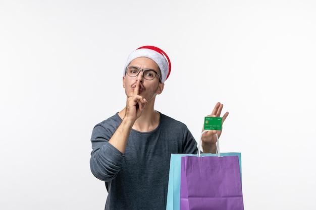 白い壁にプレゼントと銀行カードを持つ若い男の正面図