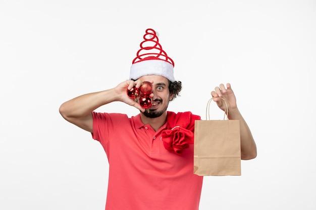 白い壁にプレゼントやおもちゃと若い男の正面図