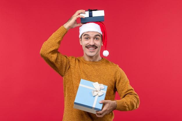 赤い壁にプレゼントと若い男の正面図