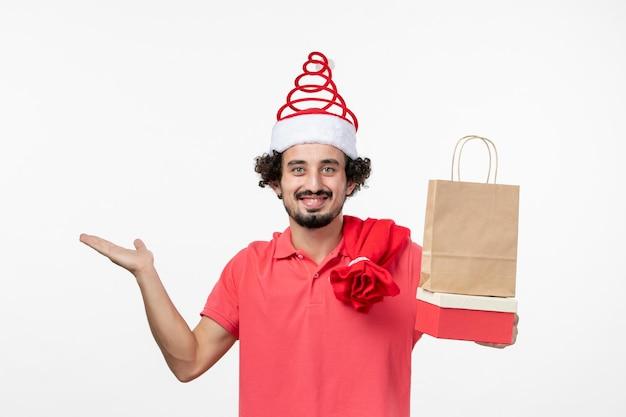 白い壁にプレゼントと若い男の正面図