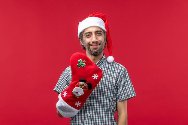 Вид спереди молодого человека в красной рождественской шапке на красной стене