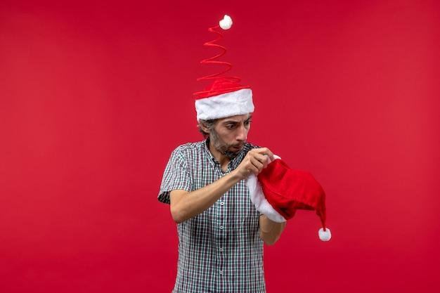 빨간 벽에 빨간 크리스마스 모자와 젊은 남자의 전면보기