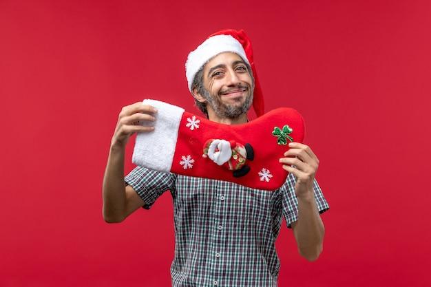 Вид спереди молодого человека с красным рождественским носком на красной стене