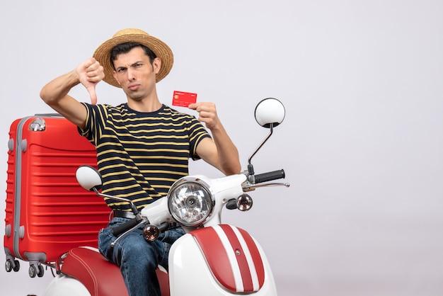 Вид спереди молодого человека в соломенной шляпе на мопеде, держащего кредитную карту, давящего большой палец вниз