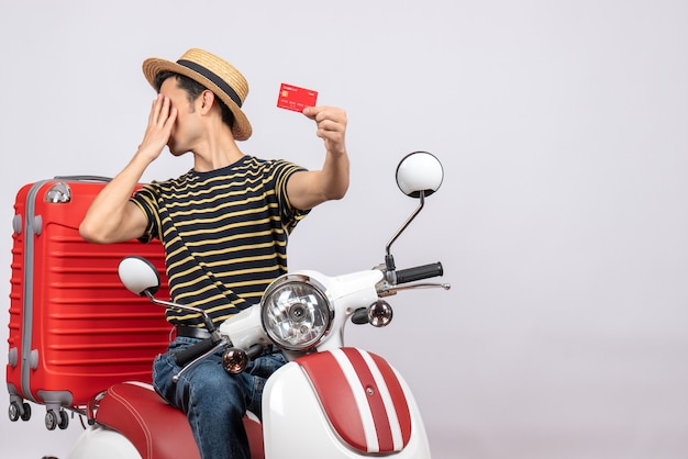 Вид спереди молодого человека в соломенной шляпе на мопеде, держащего кредитную карту, пряча лицо