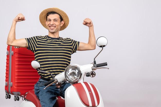 腕の筋肉を示す原付に麦わら帽子をかぶった若い男の正面図