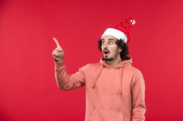 赤い壁に驚いた表情で若い男の正面図