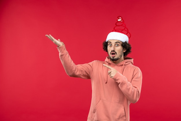 빨간 벽에 놀란 된 표정으로 젊은 남자의 전면보기