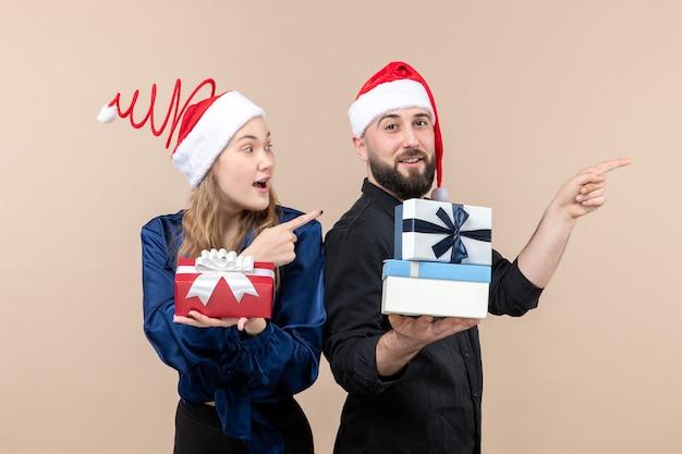 ピンクの壁にプレゼントを保持している女性と若い男の正面図