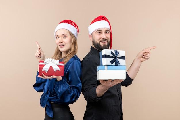 Вид спереди молодого человека с женщиной, держащей подарки на розовой стене