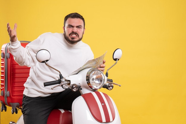 Вид спереди молодого нервного человека, сидящего на мотоцикле с чемоданом на нем, держа карту на изолированном желтом фоне