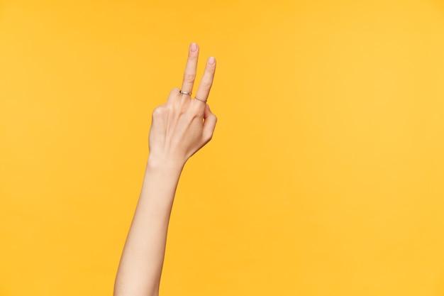 黄色の背景の上にポーズをとって、カウントしながら2本の指を上げたままの女性の若いかわいい手の正面図。手ジェスチャーとサインの概念