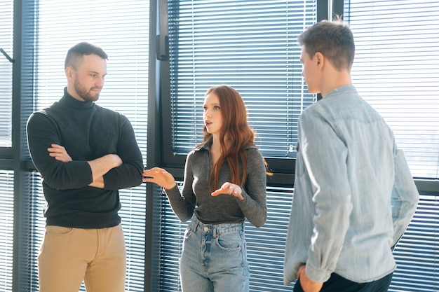 창문 근처의 현대적인 사무실에서 남성 동료들과 대화를 나누는 젊은 빨간 머리 여성 사업가의 앞모습. 부하직원은 상사의 지시에 귀를 기울인다.