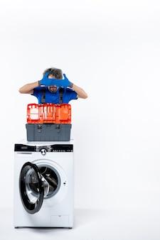 흰 벽에 그의 얼굴 세탁기를 덮고 있는 젊은 수리공의 전면 모습