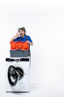 흰 벽에 있는 세탁기 뒤에 나를 부르는 젊은 수리공의 전면 모습