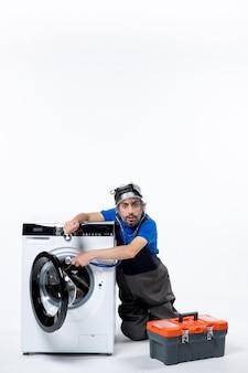 흰 벽에 세탁기를 여는 젊은 수리공의 전면 모습
