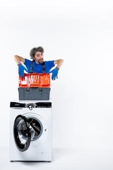 흰 벽에 세탁기에 도구 가방을 여는 젊은 수리공의 전면 보기