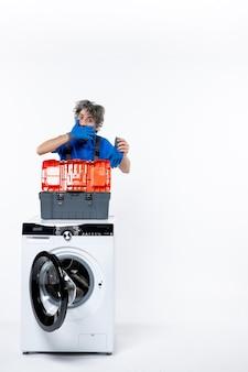흰 벽에 있는 세탁기 뒤에 손을 대고 있는 젊은 수리공의 전면 모습
