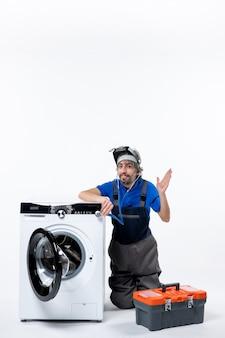 白い壁に手を上げて洗濯機の近くに座っている若い修理工の正面図