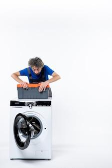 흰 벽에 도구 가방을 여는 세탁기 뒤에 서 있는 젊은 수리공의 전면 모습