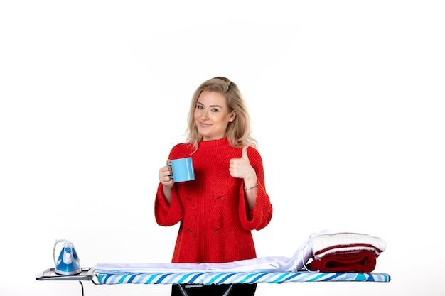 흰색 바탕에 확인 제스처를 하는 파란색 컵을 들고 다림판 뒤에 서 있는 만족스러운 젊은 여성의 전면 모습