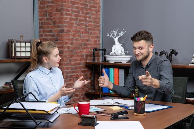 テーブルに座ってオフィスの1つの重要な問題を議論している若い満足したオフィスチームの正面図