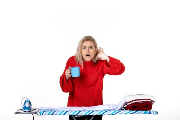 흰색 배경에 초점을 맞춘 파란색 컵을 들고 다림판 뒤에 서 있는 진지한 젊은 여성의 전면
