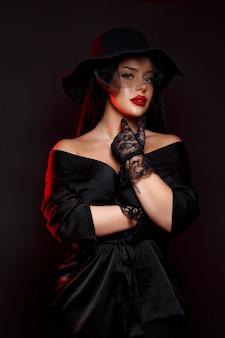Вид спереди молодой сексуальной женщины, позирующей изолированной на черной стене