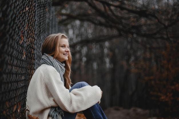 가을 숲에서 그물 근처에 앉아 웃는 젊은 백인 여자의 전면 보기