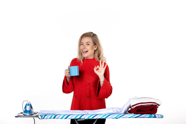 흰색 배경에 안경 제스처를 만드는 파란색 컵을 들고 다림판 뒤에 서 있는 젊은 미소 매력적인 여성의 전면 보기